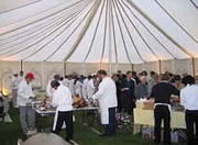 People putting food on their plates in a marquee at a hog roast event